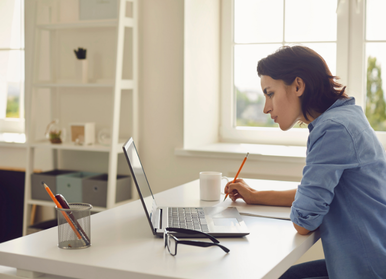 woman attending online conference taking notes